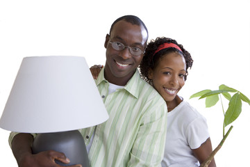 Woman with pot plant embracing husband, man carrying lamp, smiling, portrait, cut out