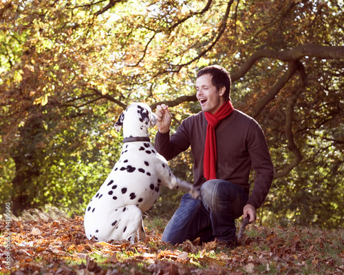 A young man playing with his dog amongst the autumn leaves