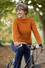 A senior woman riding a bicycle, smiling,