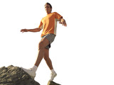 man walking up rocks with arms out, cut out