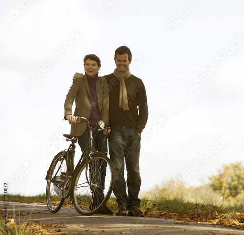 A young couple pushing a bicycle in autumn time