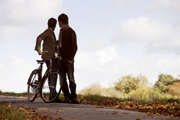 A young couple standing with a bicycle in autumn time