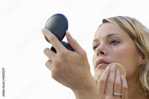 young woman applying makeup, looking in mirror, cut out