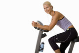 woman on exercise bike listening to music on earphones, cut out