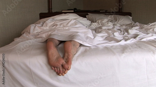 Woman lying in bed and stretching her feet