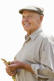 senior man in flat cap holding corn, cut out