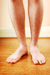 A man's naked legs standing on wooden floor