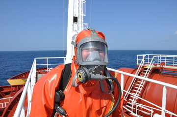 man in chemical suit on deck of chemical tanker