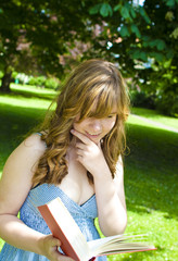 Student reading a book in a park