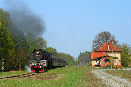 Steam passenger train starting from the small station