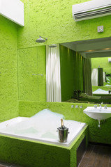 Green modern bathroom with jacuzzi full of bubbles.
