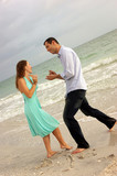 couple pretending to propose on beach poster