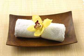 Spa essentials ( towel and orchid on wooden bow