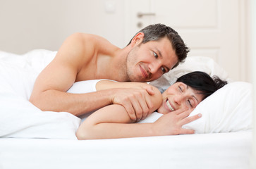 liebespaar im bett beim kuscheln im schlafzimmer