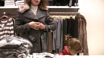 mother with little girl try fit clothes in shop