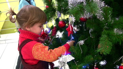 little girl watching christmas tree in shop