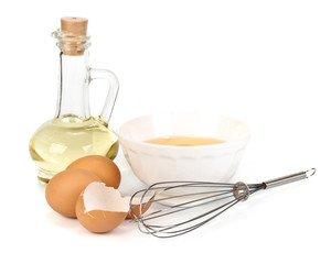 Eggs, oil, cup of milk and whisk