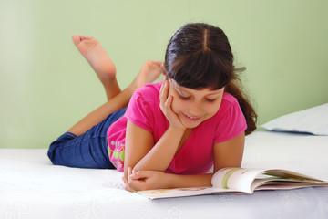 Niña leyendo libro en la cama