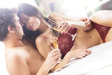 Fototapety Couple kissing and drinking champagne on the bed
