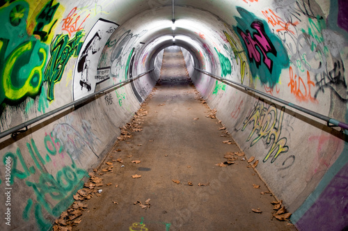 In de dag Tunnel A long pedestrian tunnel covered with graffiti and neon lights