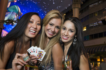 Portrait of three young women with playing cards, gambling chips and champagne in front of casino, Las Vegas, Nevada, USA