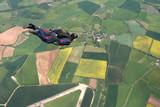 Skydiver flies past cameraman poster