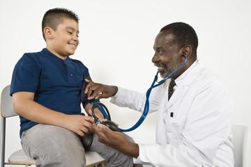Doctor examining pre-teen 10-12 boy