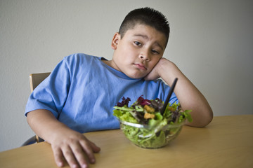 Pre-teen 10-12 boy sitting at desk with salad