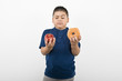 Pre-teen 10-12 boy holding doughnut and apple