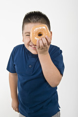Pre-teen 10-12 boy holding doughnut over eye