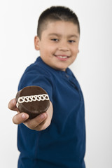 Pre-teen 10-12 boy holding out cookie