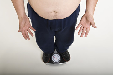 Low section of man standing on bathroom scale