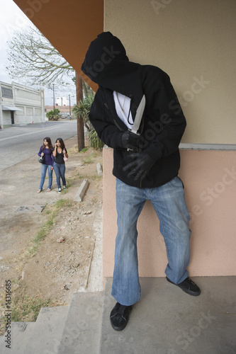 Robber with knife hiding behind corner and waiting for two girls