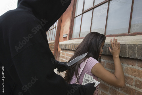 Hooded man robbing young woman with knife