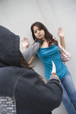 Hooded woman robbing young woman with knife