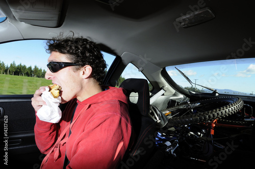 Man driving car while eating from bag