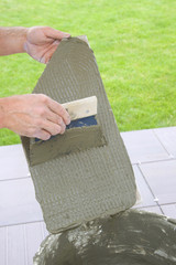 tile-layer who poses tiling on a terrace