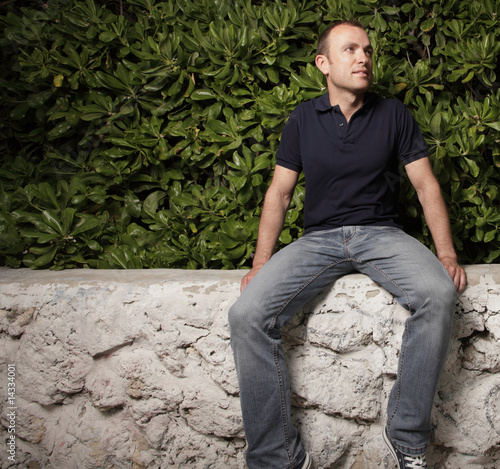 Casual man sitting on a ledge