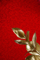 Gold branch on red background