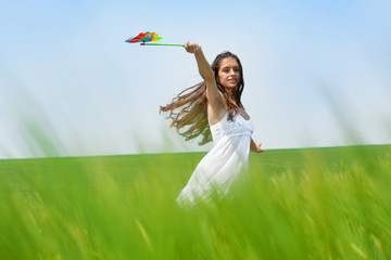 girl running through green field with colorful hand mill