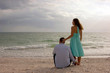 beautiful image of two young lovers at the beach at sunset looki