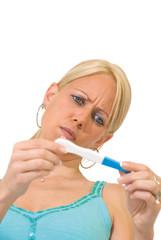 Femme blonde en train de lire un test de grossesse