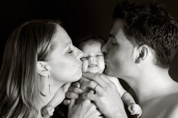 Schwarz-Weiss: Junge Eltern küssen ihr Baby