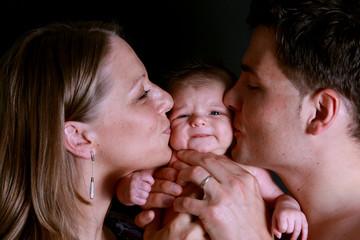 Junge Eltern küssen ihr Baby