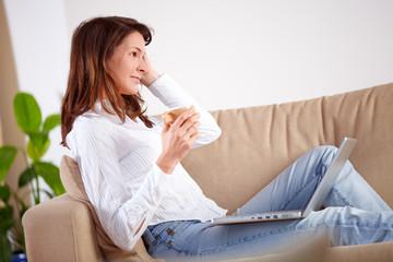 Frau mit Laptop und Kaffeetasse