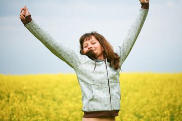 Happy girl with fluttering hair in flower field