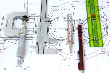 Micrometer, Caliper, Pencil, Compass and ruler on Blueprint