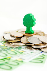 Ecology concept, a toy tree on a pile of money