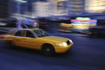 Taxi cab speeding down a city street at night