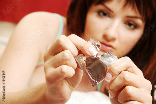 Woman opening condom
